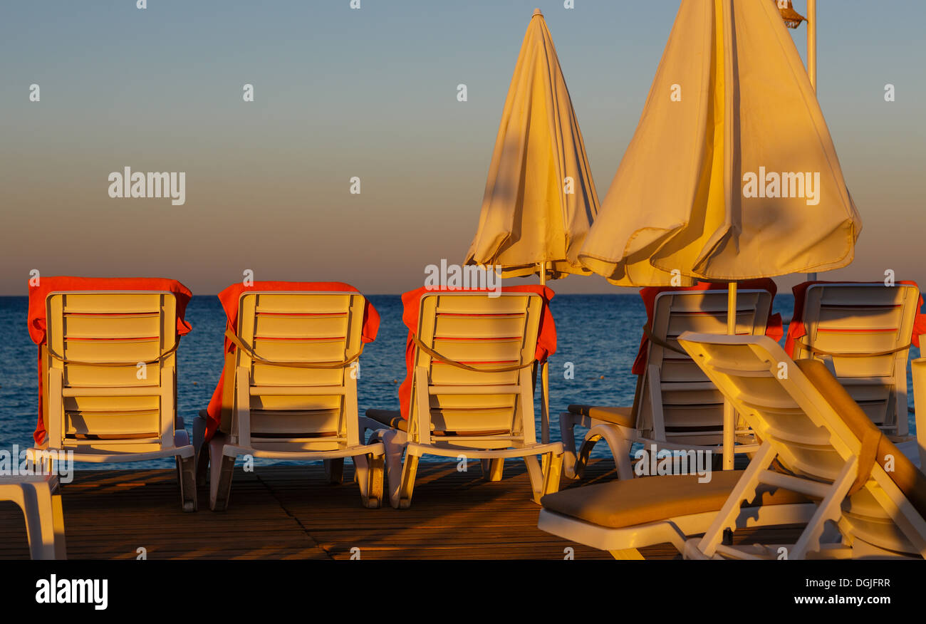 Chaise Lounges And Sunshade Umbrellas In Light Of Rising Sun Stock