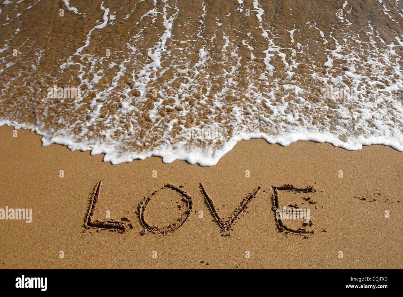 'Love' written in the sand on the beach - Stock Image