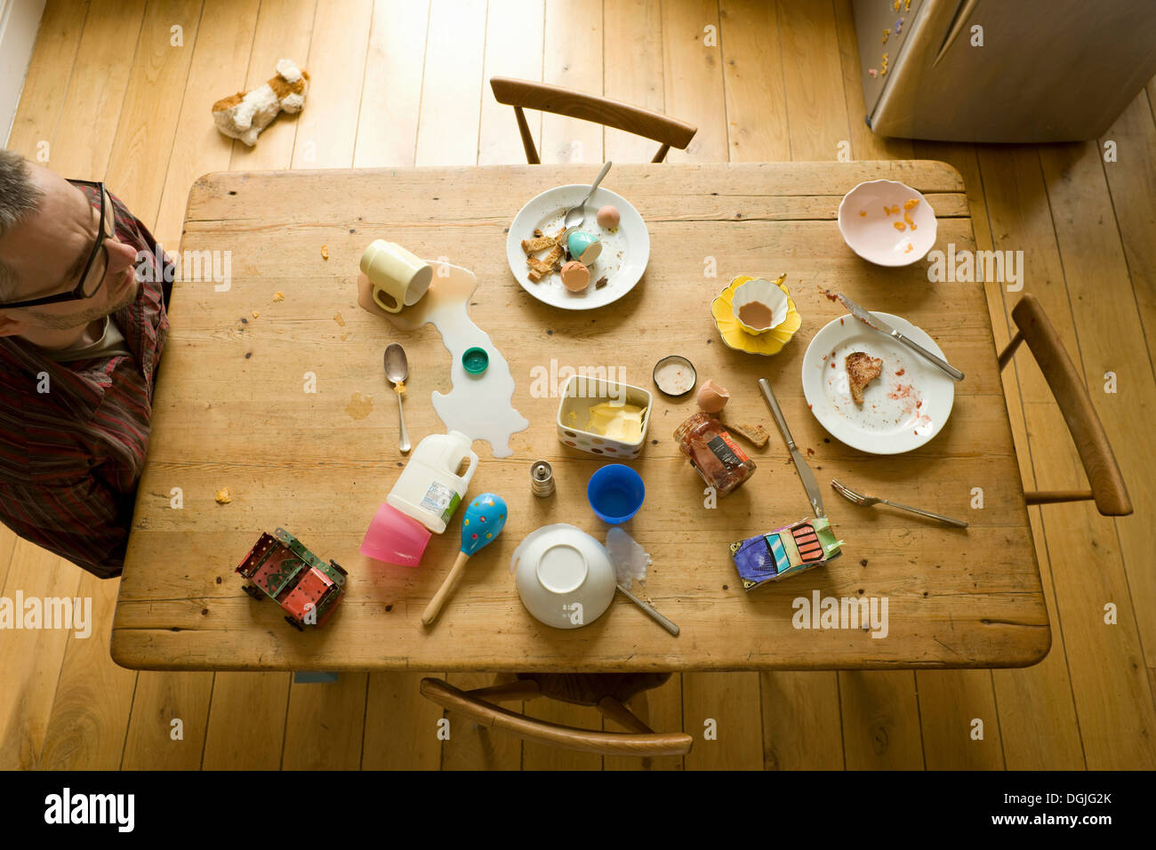 Overhead view of mature man sitting alone at messy breakfast table - Stock Image
