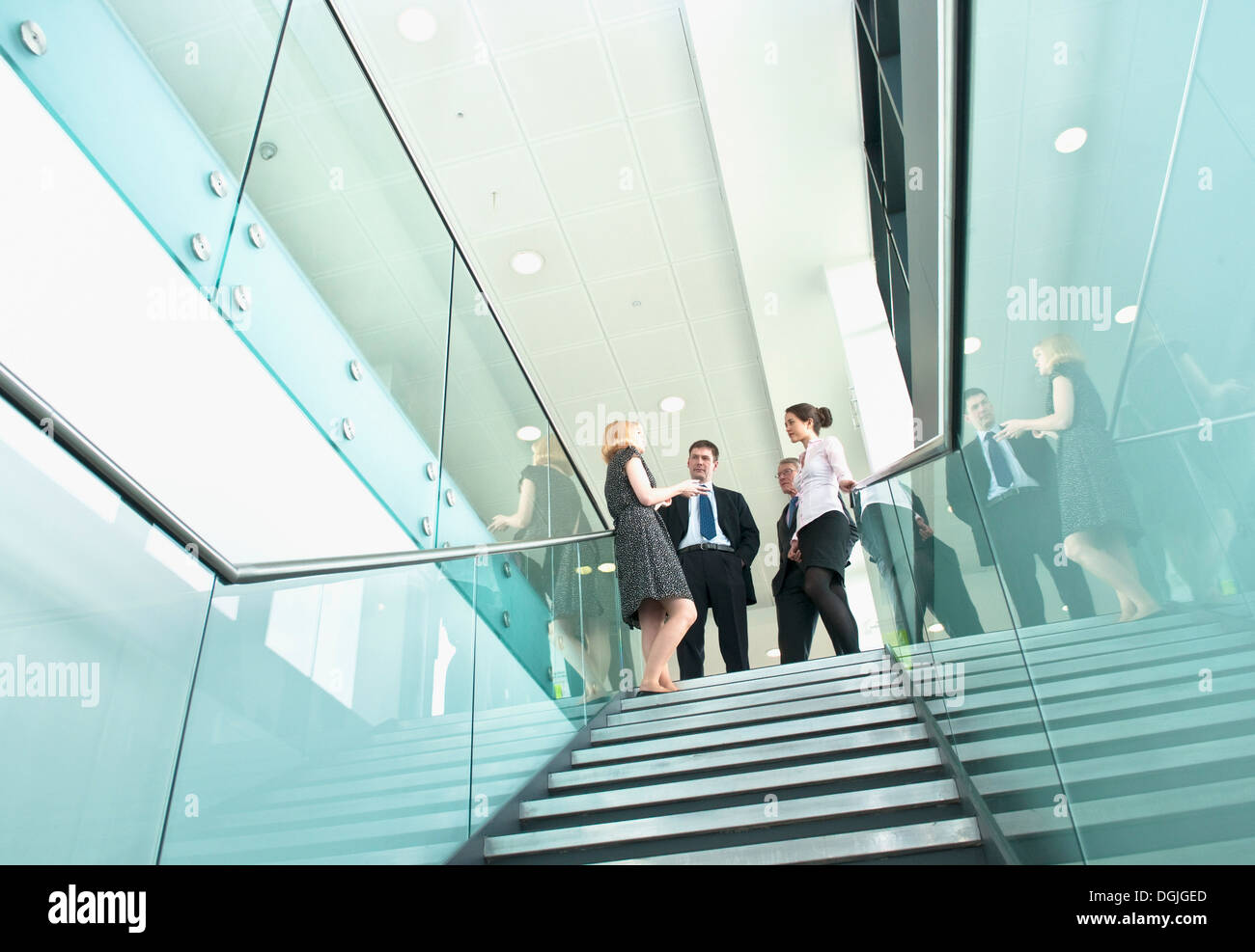 Colleagues standing on staircase in office building - Stock Image