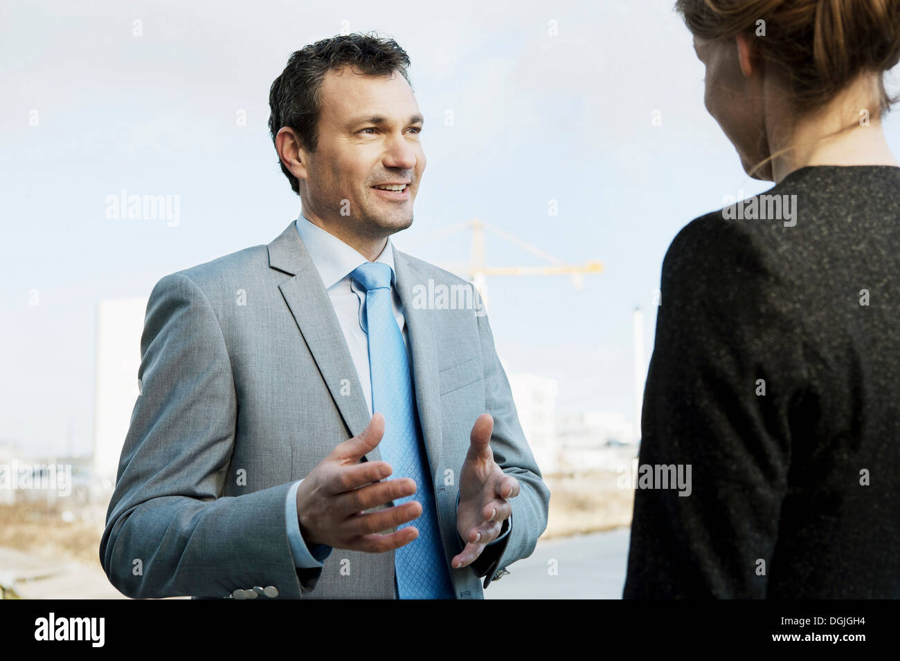 Mature businessman speaking to colleague outdoors - Stock Image