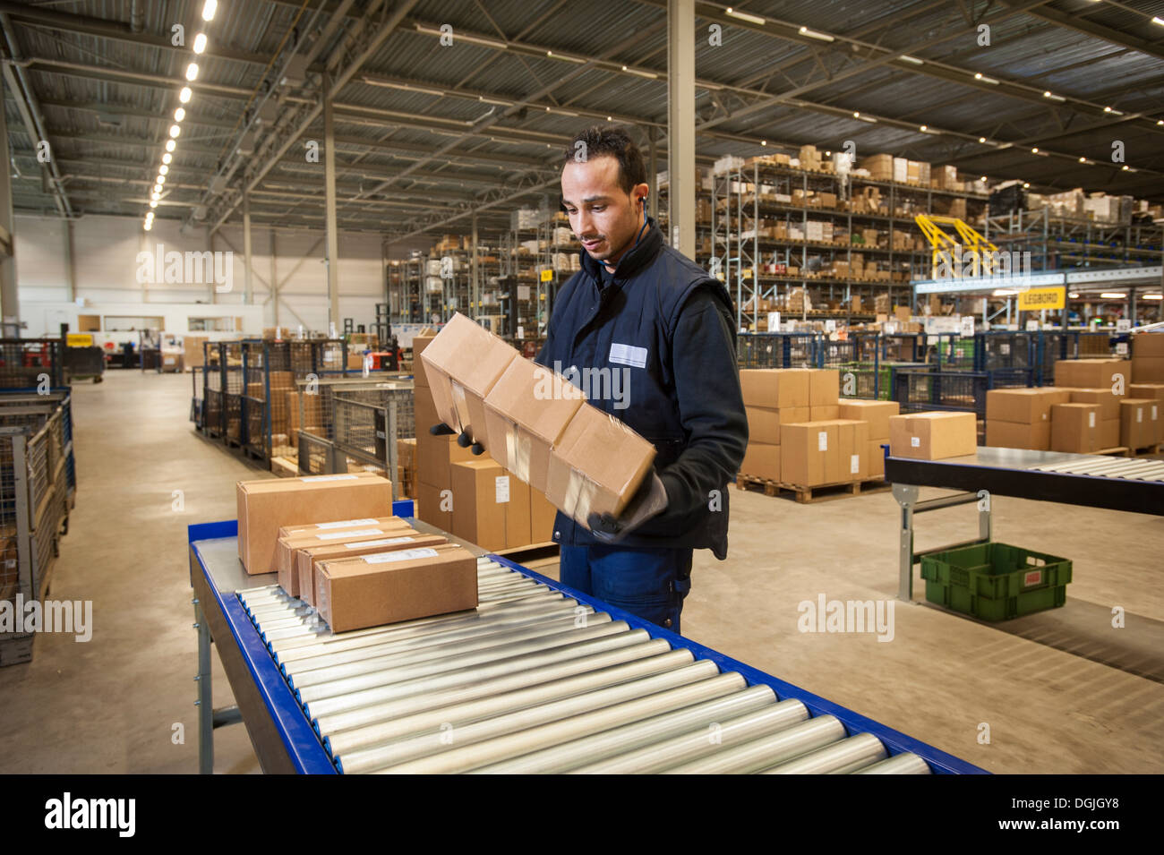 Male warehouse worker selecting cardboard boxes from conveyor belt - Stock Image