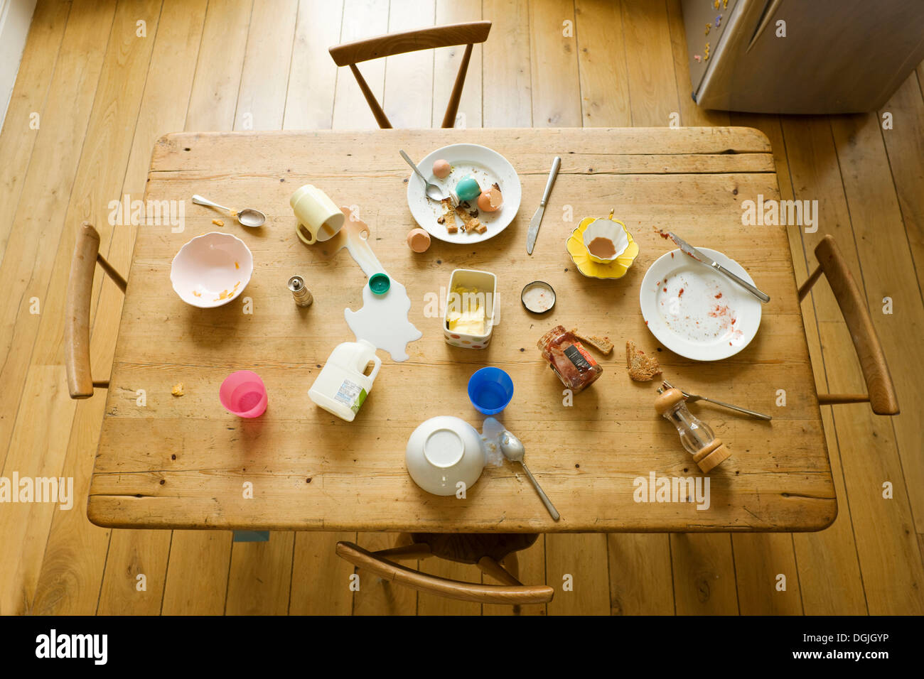 Overhead view of breakfast table with eaten food and messy plates - Stock Image