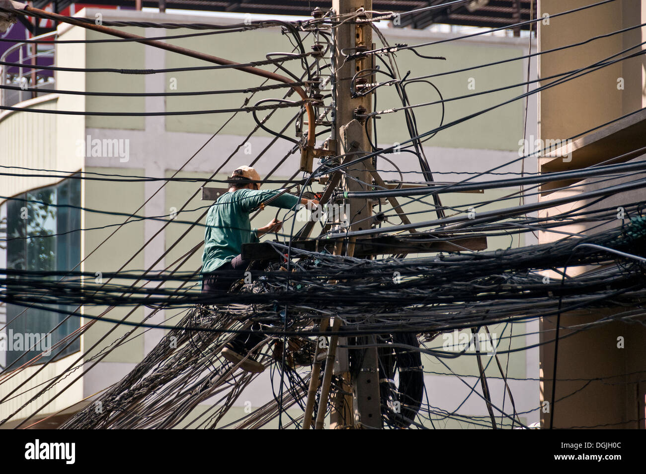 A Thai telephone engineer installing a cable on a telegraph pole in ...