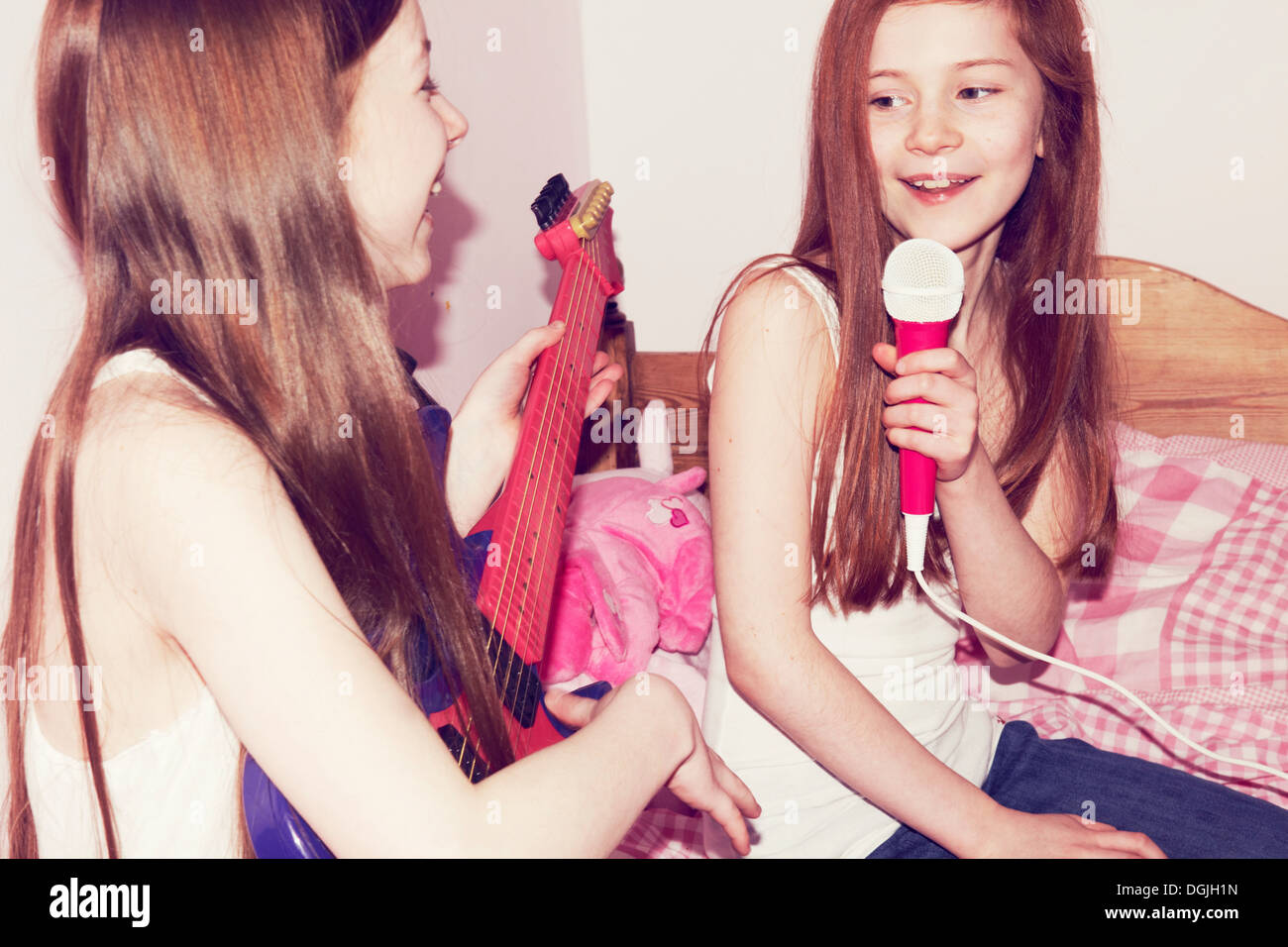 Two girls playing guitar and singing into microphone in bedroom - Stock Image