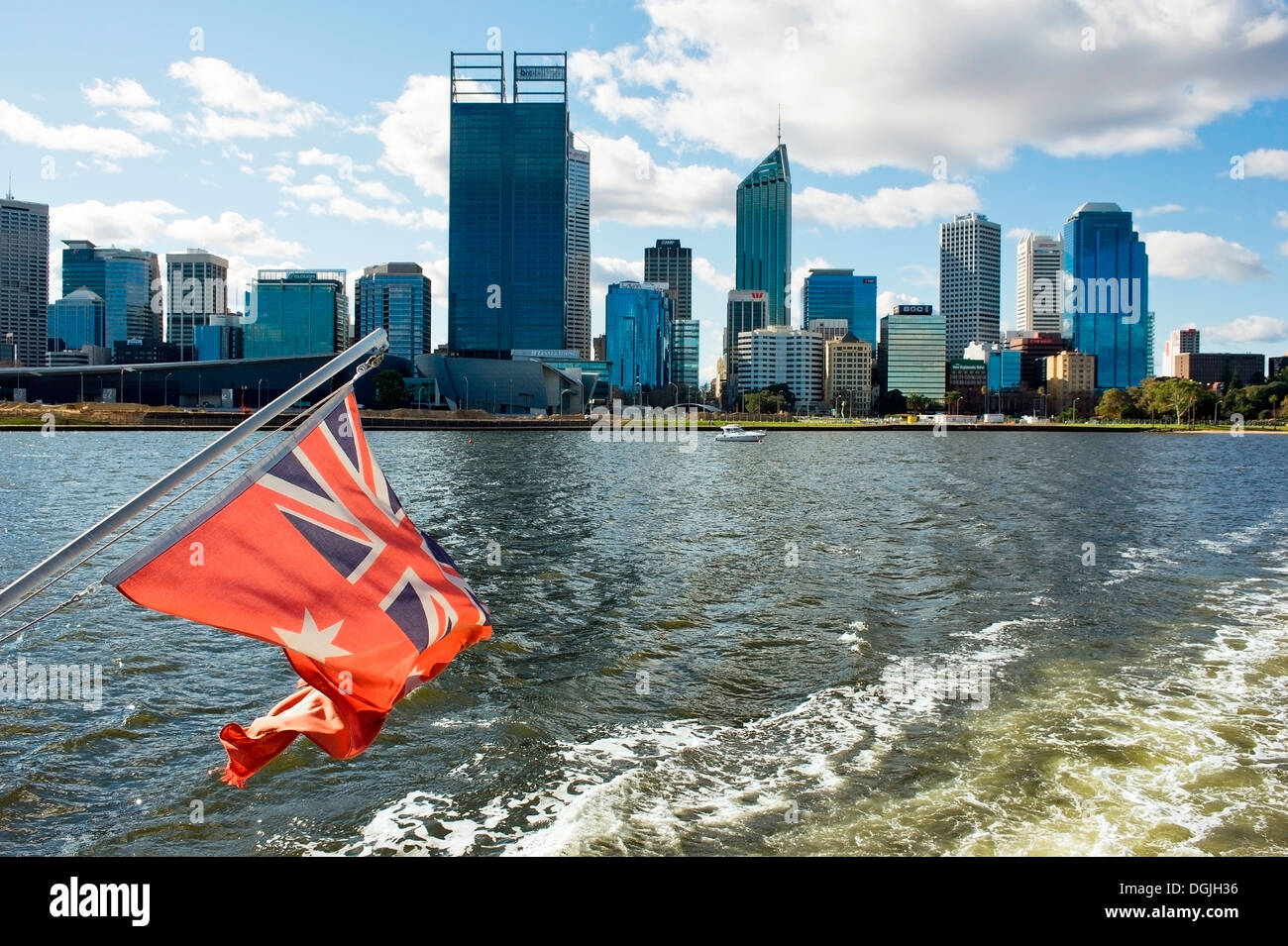 The Australian Red Ensign flown on a boat as it sails past the city of Perth. - Stock Image