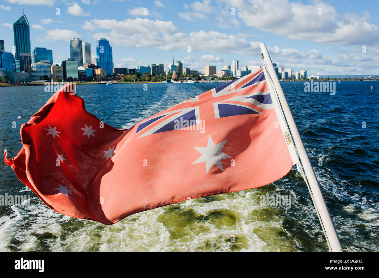 The Australian Red Ensign flown on a boat as it departs the city of Perth. - Stock Image