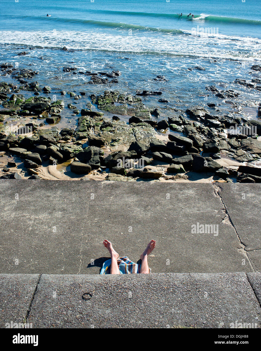The legs of a sunbather at Alexandra Headland in Queensland. Stock Photo