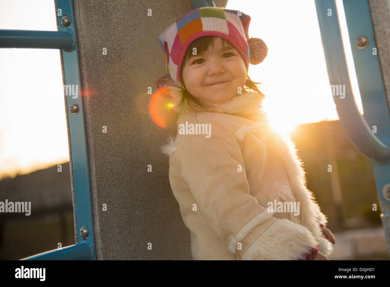 Portrait of young girl in sheepskin coat in playground - Stock Image