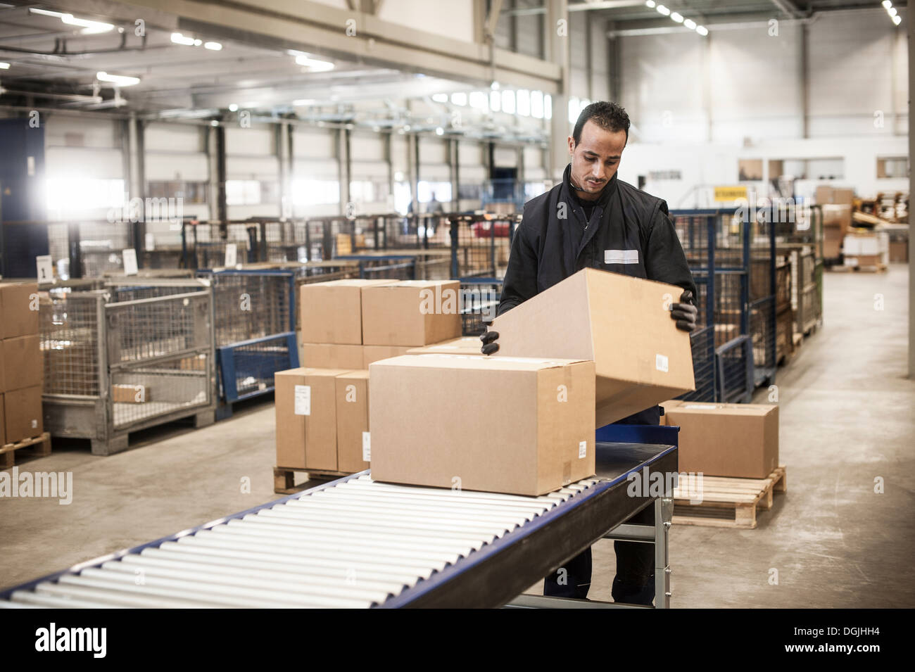 Male warehouse worker checking cardboard box from conveyor belt - Stock Image
