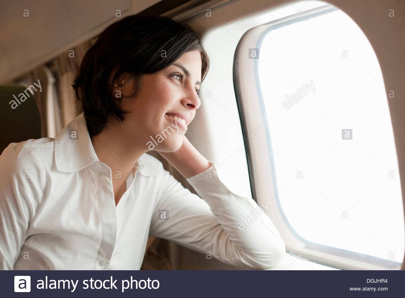 Candid portrait of young female looking out of aeroplane window - Stock Image