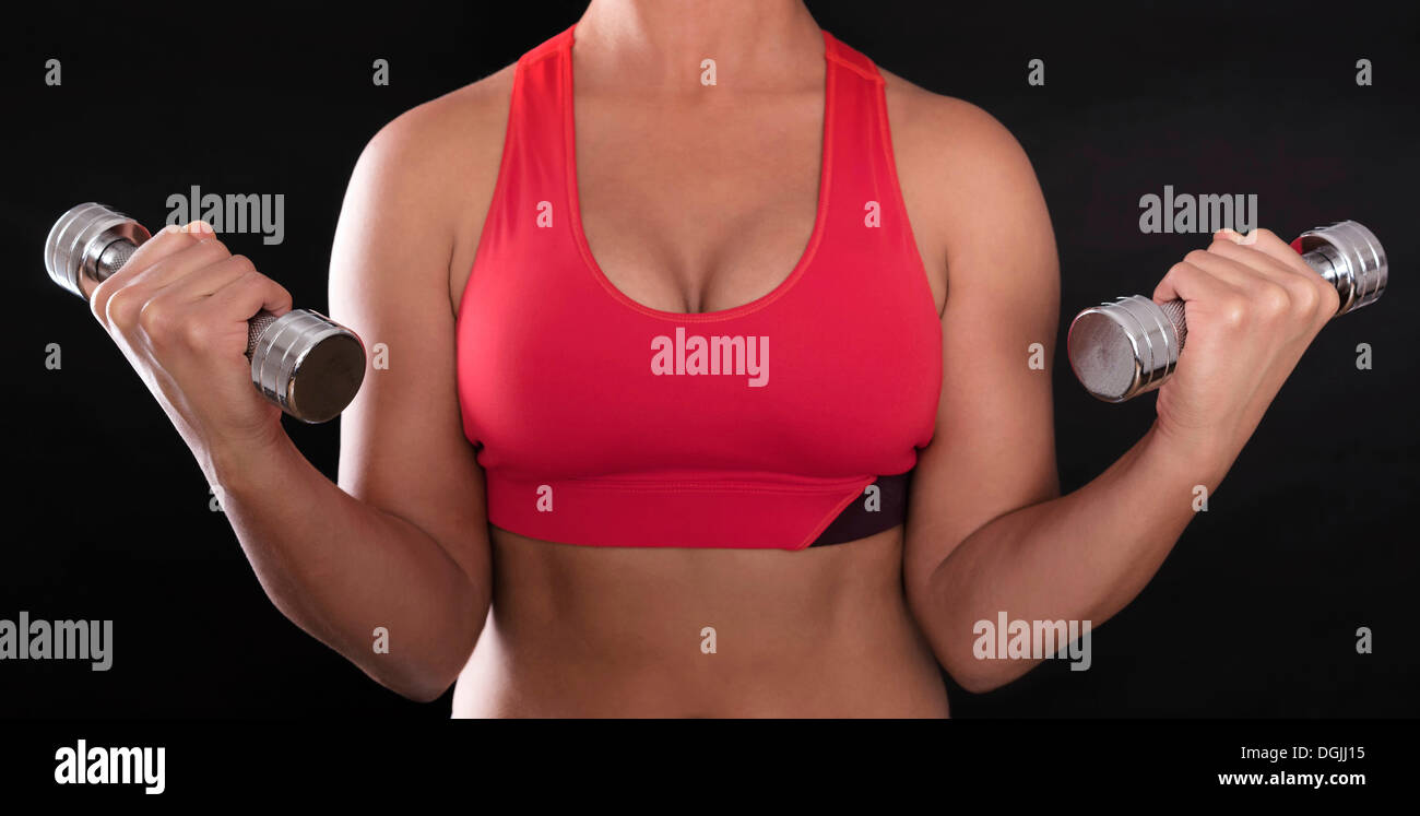 Young woman's upper body wearing a red sports bra while doing fitness training with chrome dumbbells - Stock Image