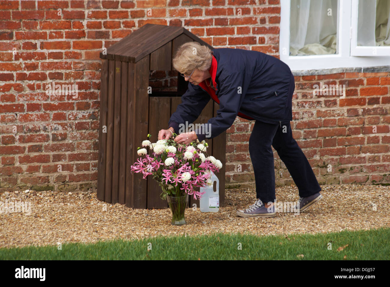 woman tidying up bunch of flowers in vase at Buckler's Hard - Stock Image