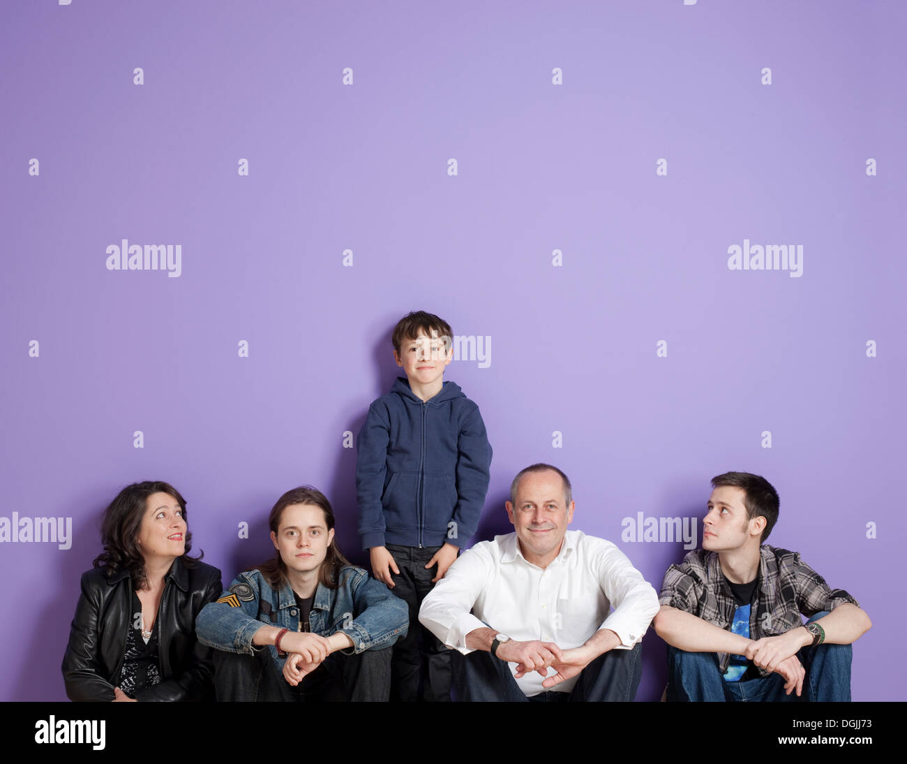 Boy standing in the middle of sitting family in front of purple background - Stock Image