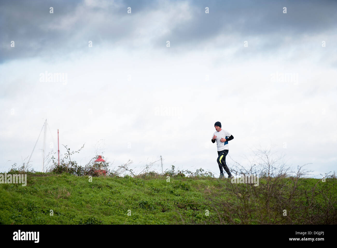 A man running along the sea wall at Tollesbury Saltings. Stock Photo