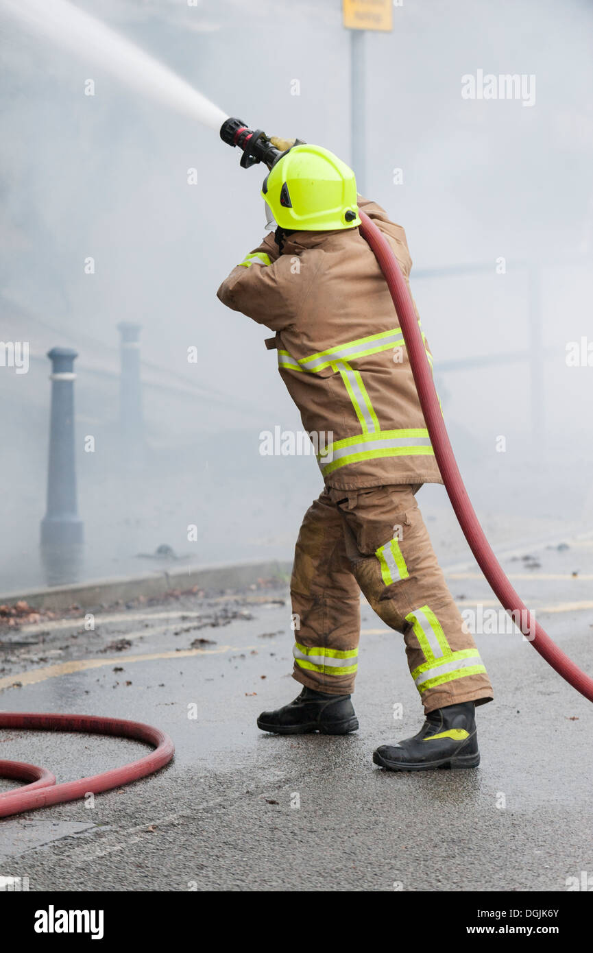 A member of the Essex Fire Service tackles a fire with a hose. - Stock Image