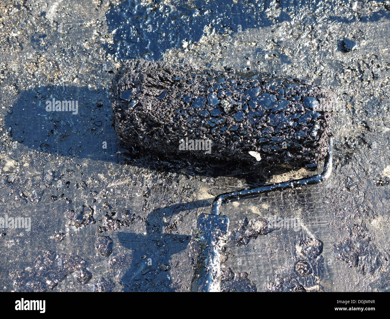 Roofer water seals a roof with tar - Stock Image