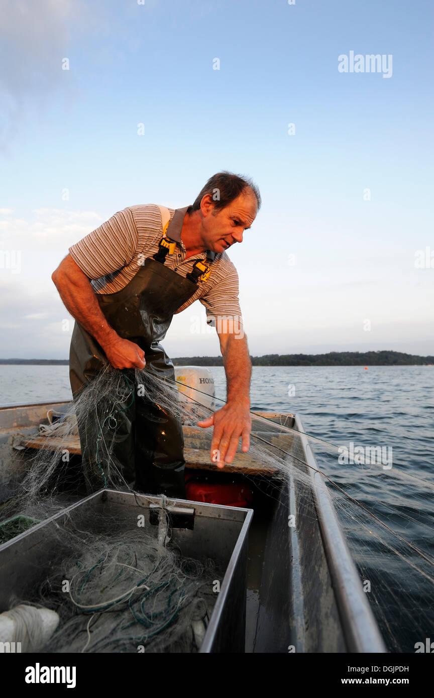 The fisherman Johann Strobl casting for fish on Lake Starnberg, Fuenfseenland area, Upper Bavaria, Bavaria - Stock Image