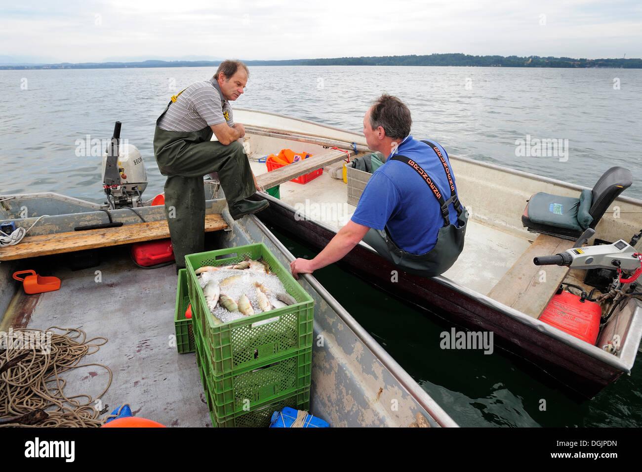 Two fishermen chatting on Lake Starnberg, Fuenfseenland area, Upper Bavaria, Bavaria - Stock Image