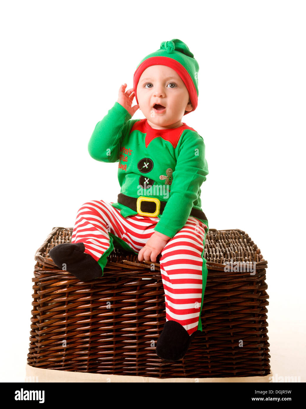 Baby in Christmas Elf costume sitting on a wicker basket, on a white studio background. - Stock Image