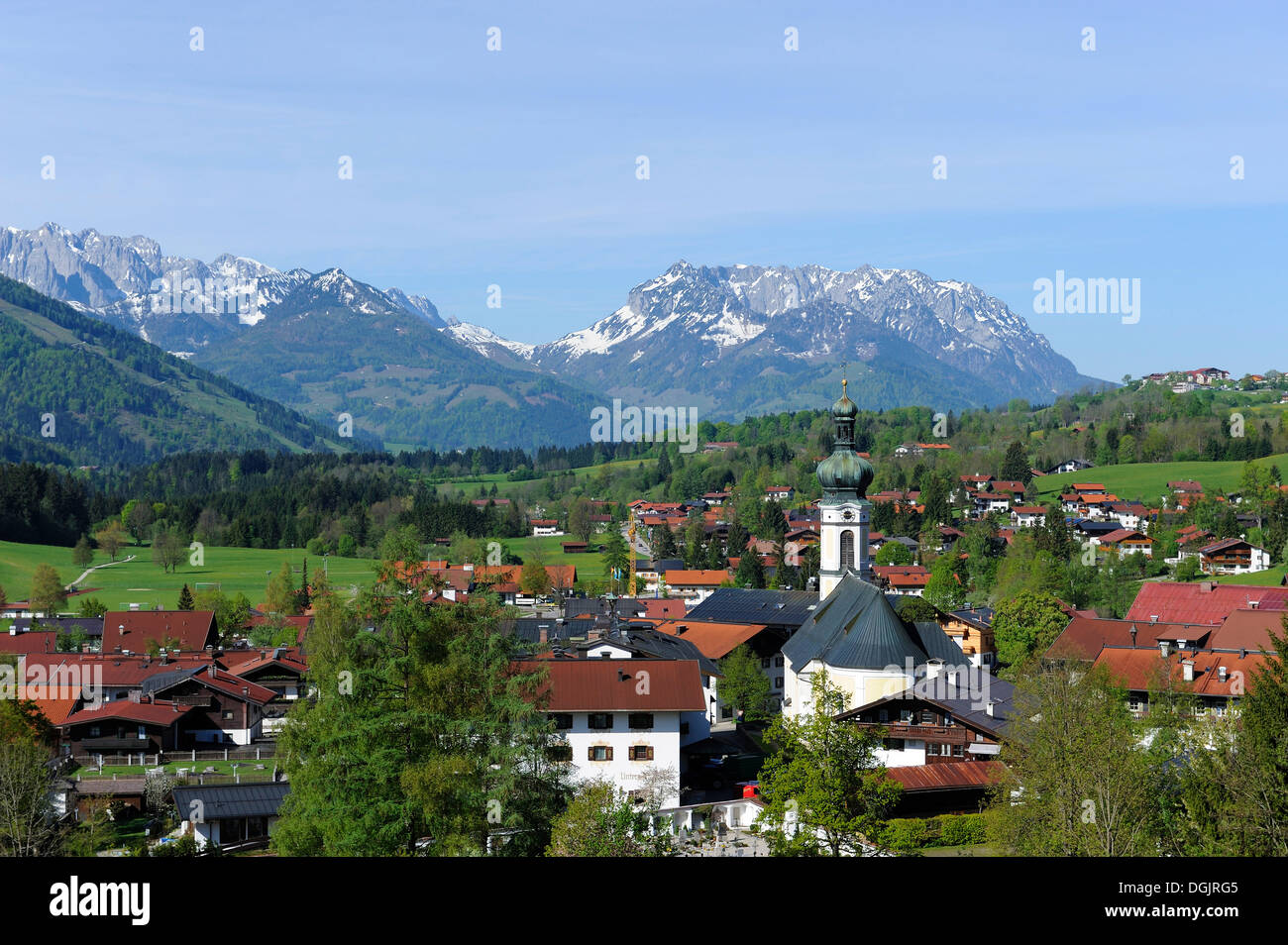 Reit im Winkl with parish church of St. Pancras, mountains Wilder Kaiser and Zahmer Kaiser at back, Chiemgau region - Stock Image