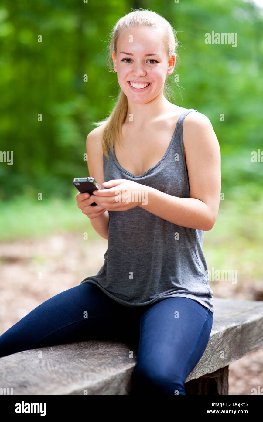 Berlin, Germany, Portrait of a young woman using her mobile phone - Stock Image