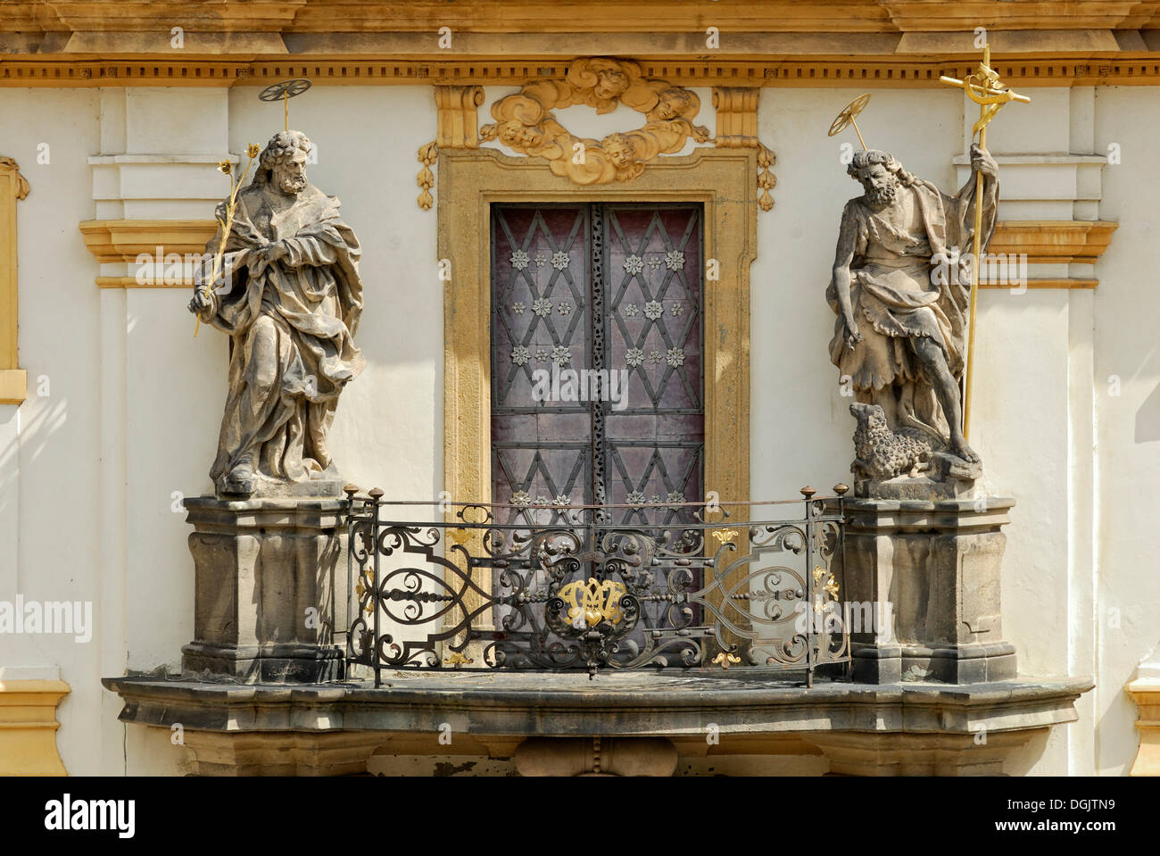 Balcony with statues of saints above the portal of Loreta Church, St. Joseph with lilies and Saint John the Baptist holding a - Stock Image