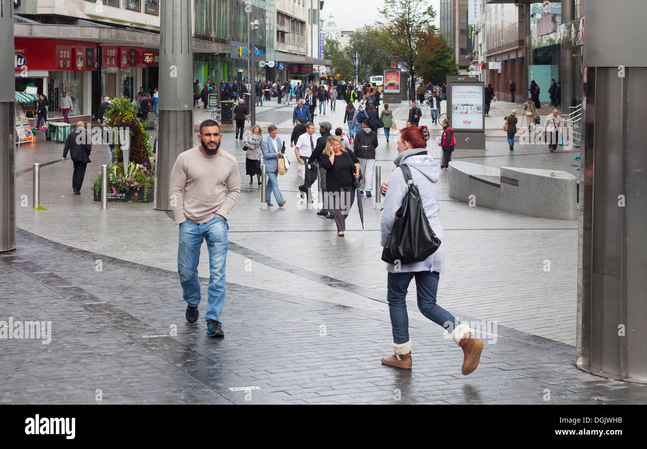 Pedestrians and shoppers on a rainy day on High Street, Birmingham, England, UK - Stock Image