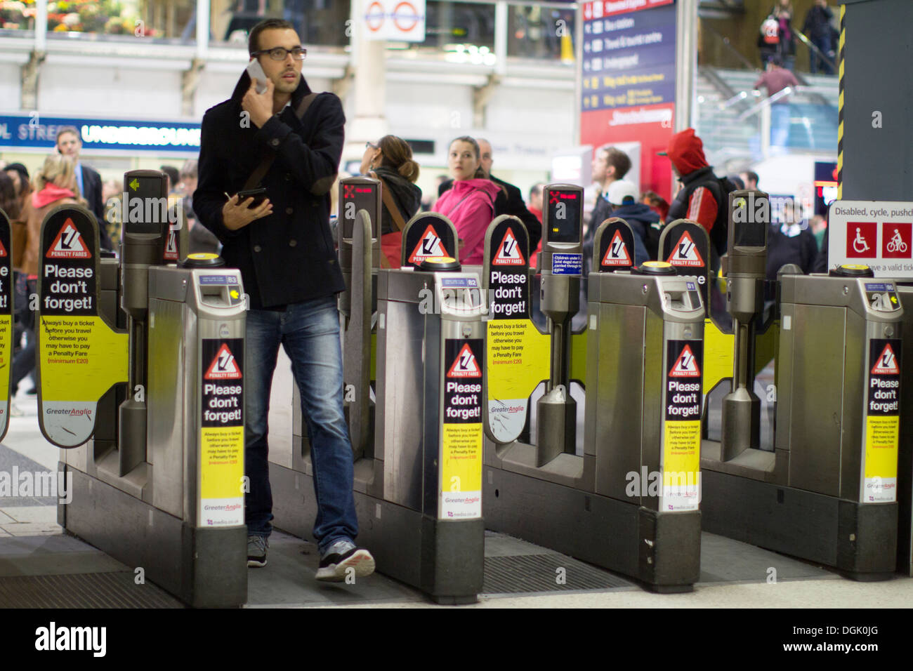 automatic ticket barrier Liverpool street station, with commuter on mobile phone - Stock Image