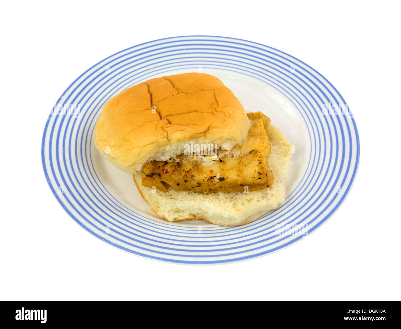 A portion of microwaved haddock between a white bread bun on a blue striped plate. - Stock Image