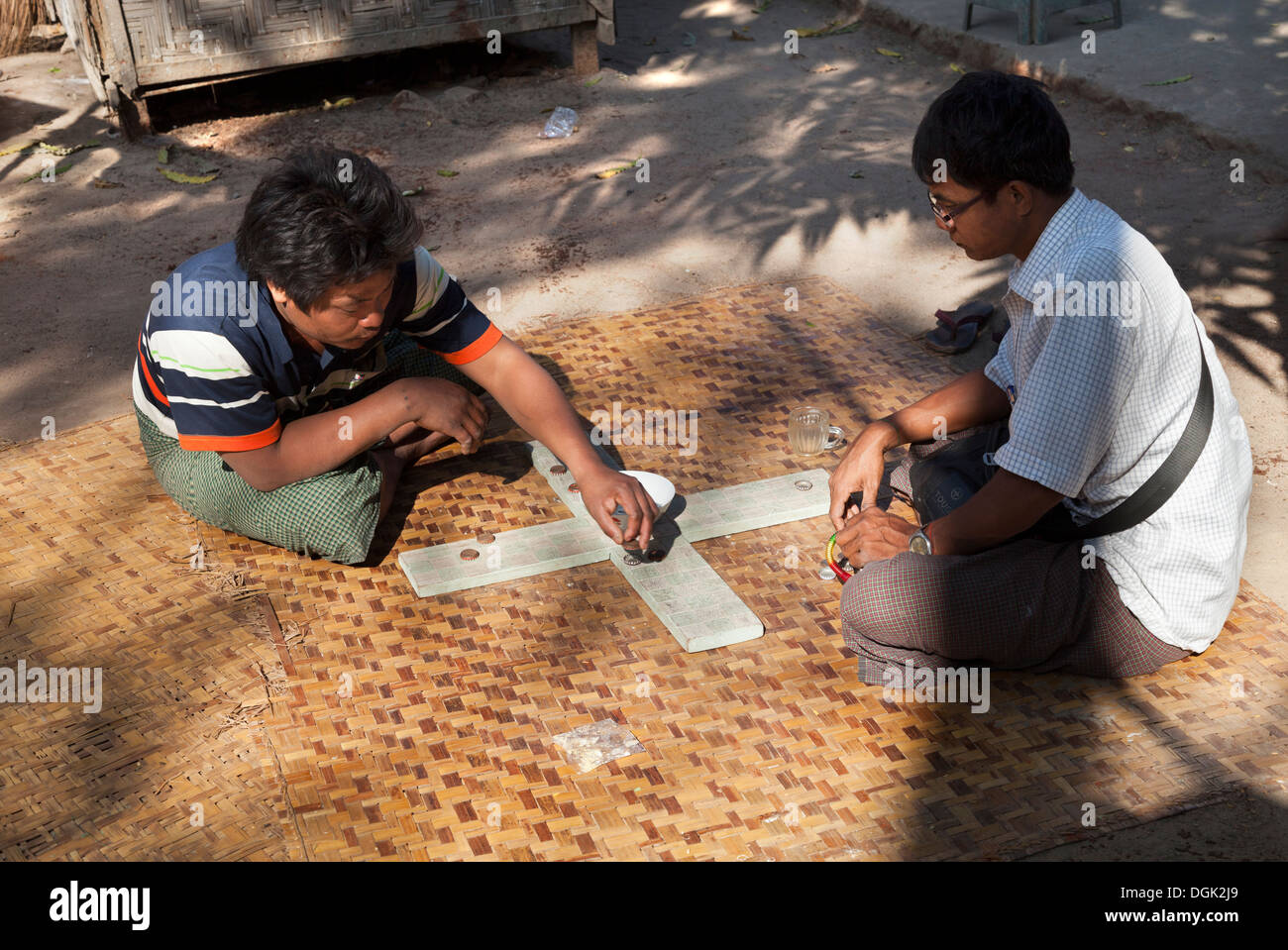 An unusual board game being played in the street in Mandalay in Myanmar. - Stock Image