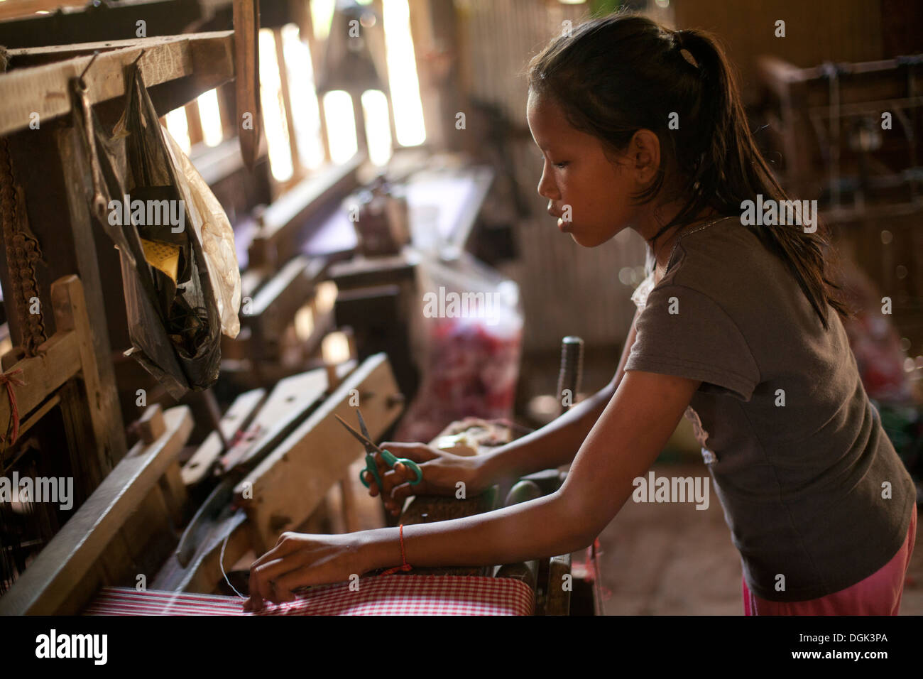 A young girl works in a village textile factory outside of Phnom Penh, Cambodia. Photos © Dennis Drenner 2013. - Stock Image
