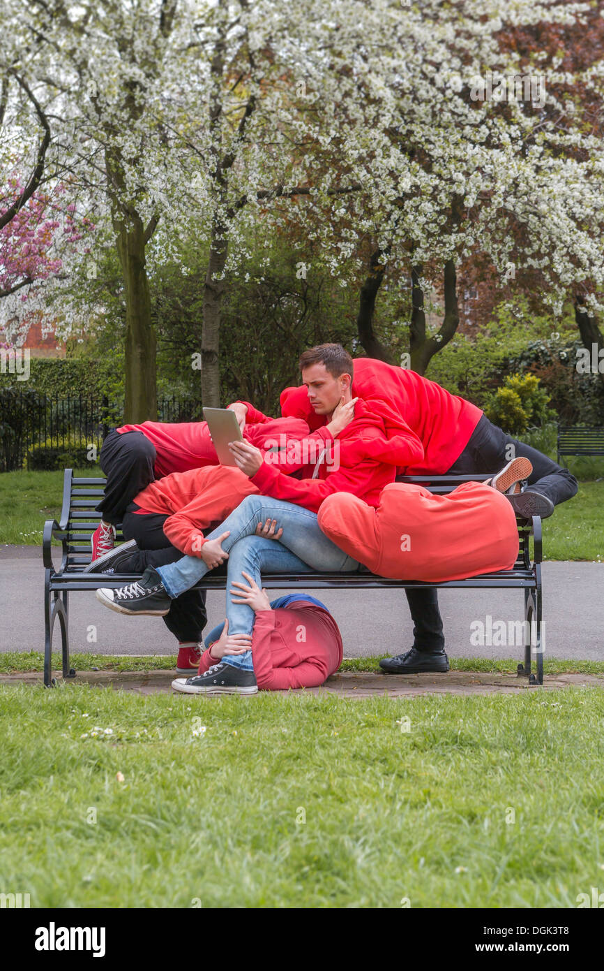 Group of young people performing on city park bench - Stock Image