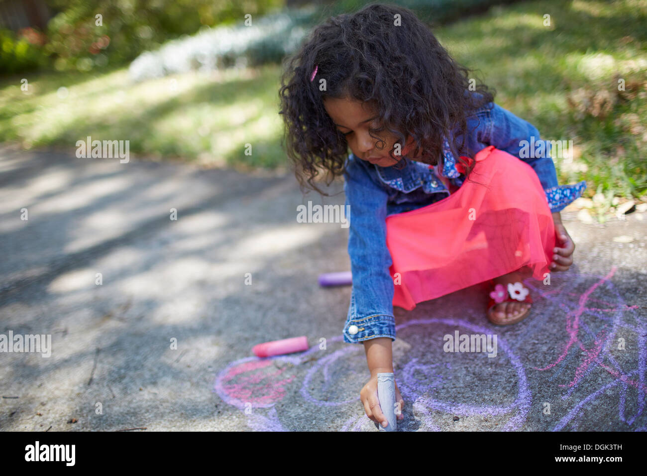 Girl drawing with chalk on the sidewalk - Stock Image