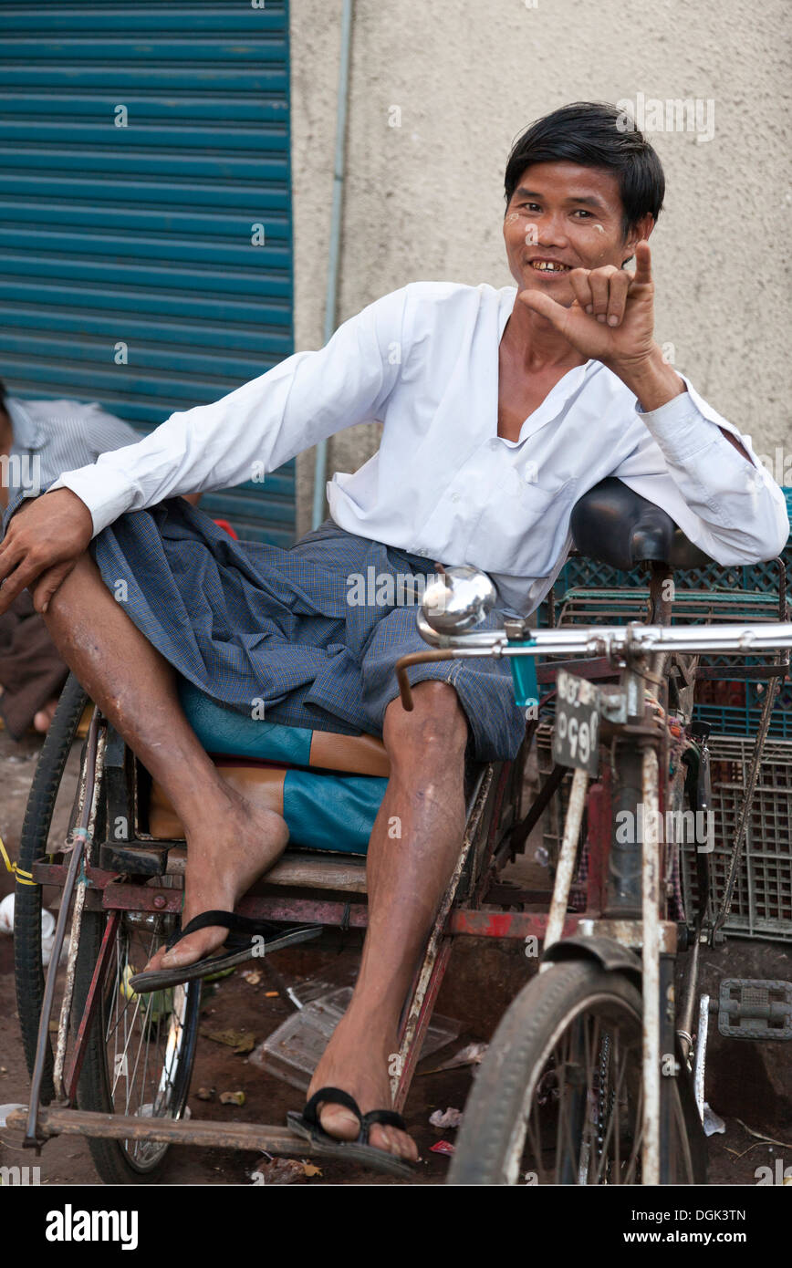 Laid-back trike rider for hire in the Indian Market in Yangon in Myanmar. - Stock Image