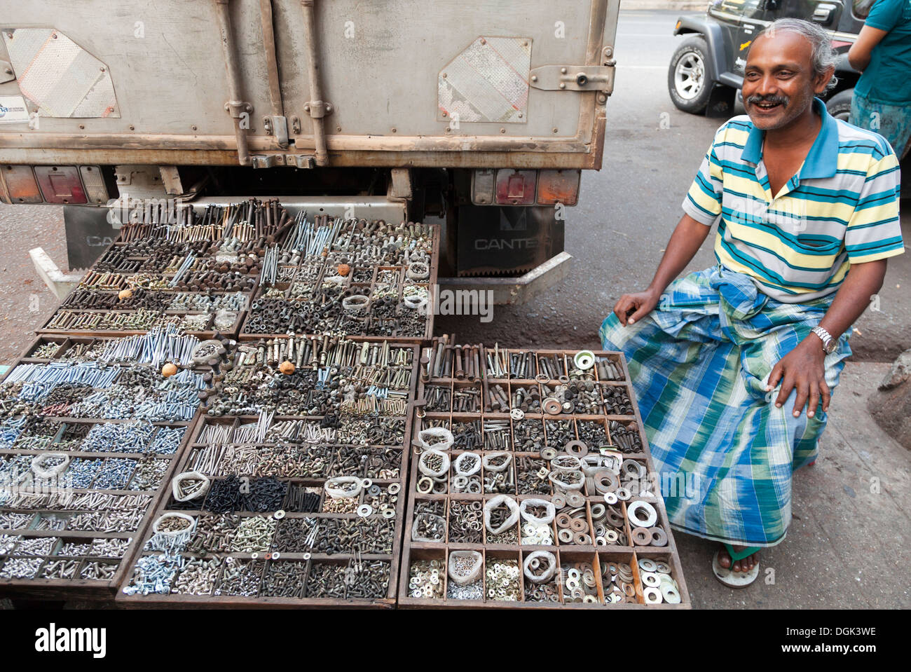 Man selling nuts and bolts in the Indian Market in Yangon in Myanmar. - Stock Image