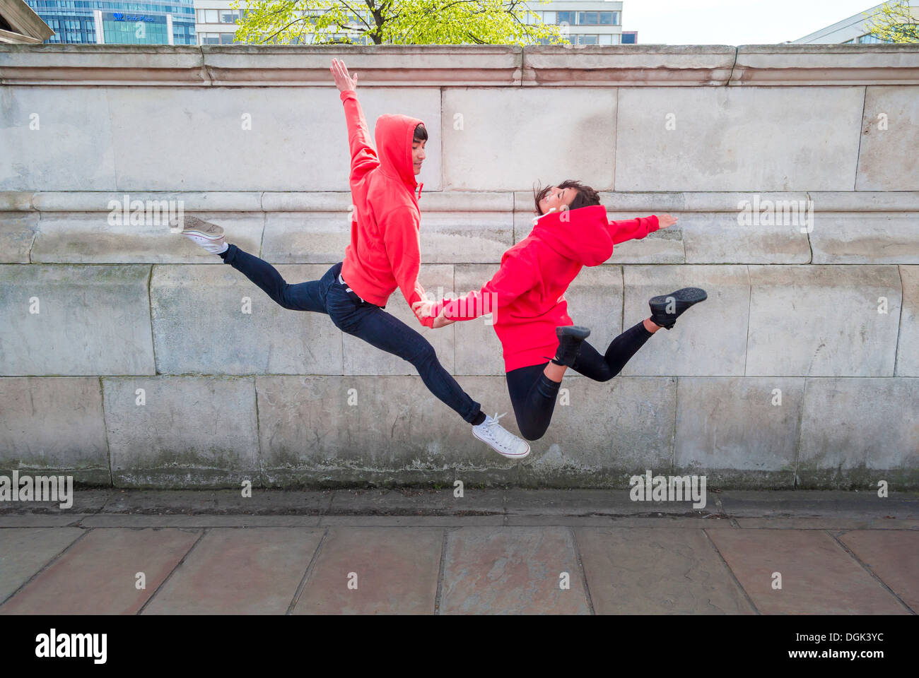 Young male and female dancer mid air in city Stock Photo