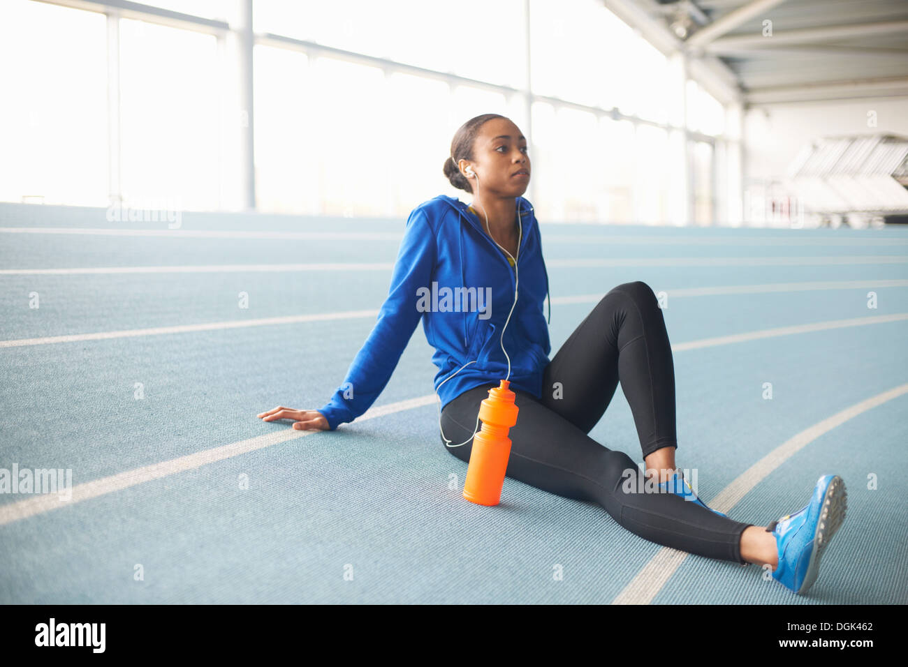 Young female athlete wearing earphones resting - Stock Image