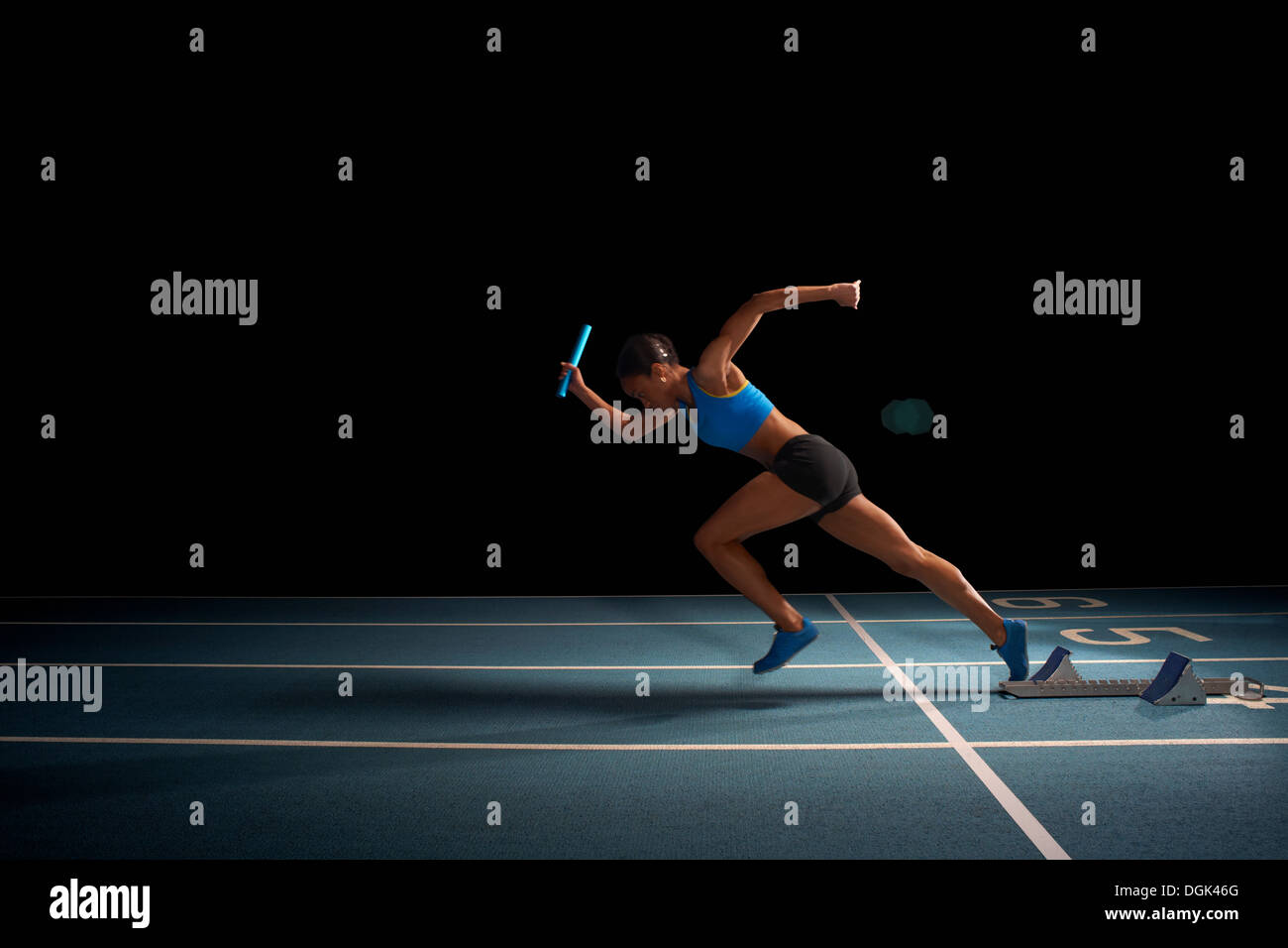 Young female athlete in relay race - Stock Image