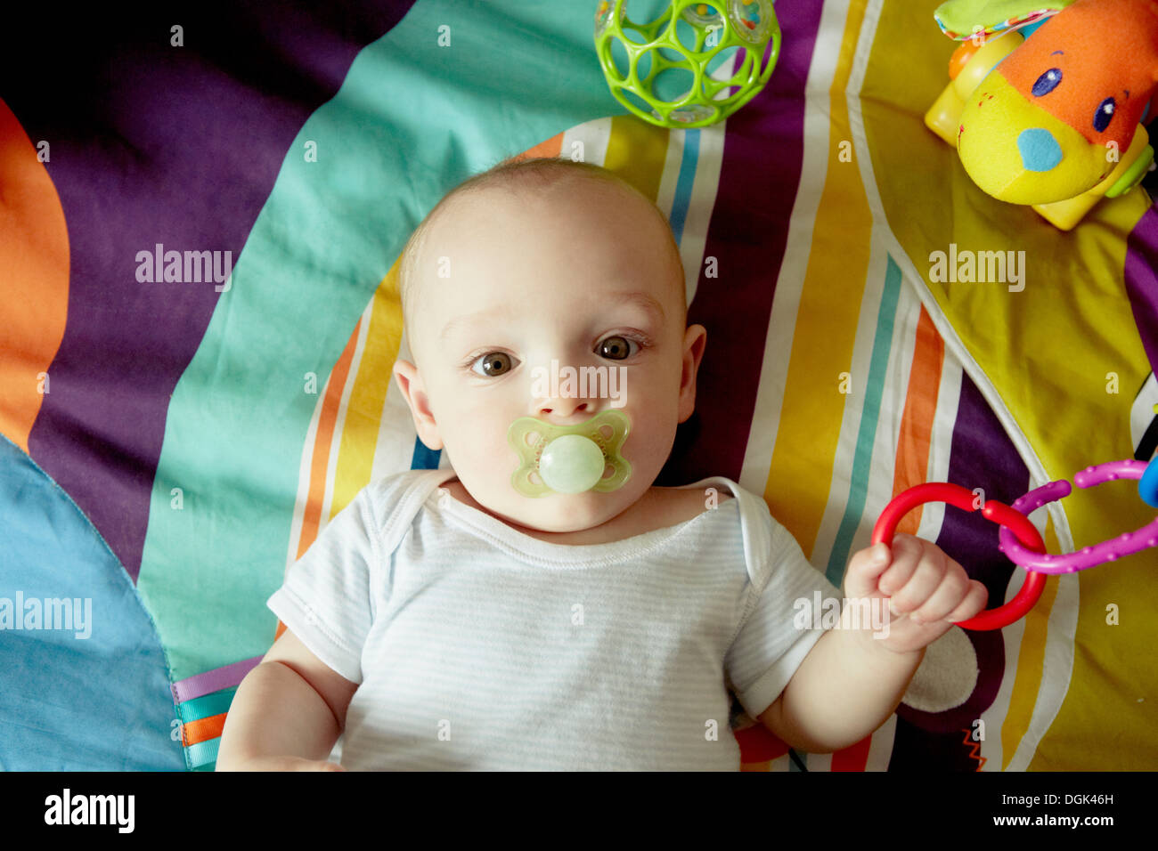 Baby boy lying on blanket sucking pacifier and playing with toys - Stock Image