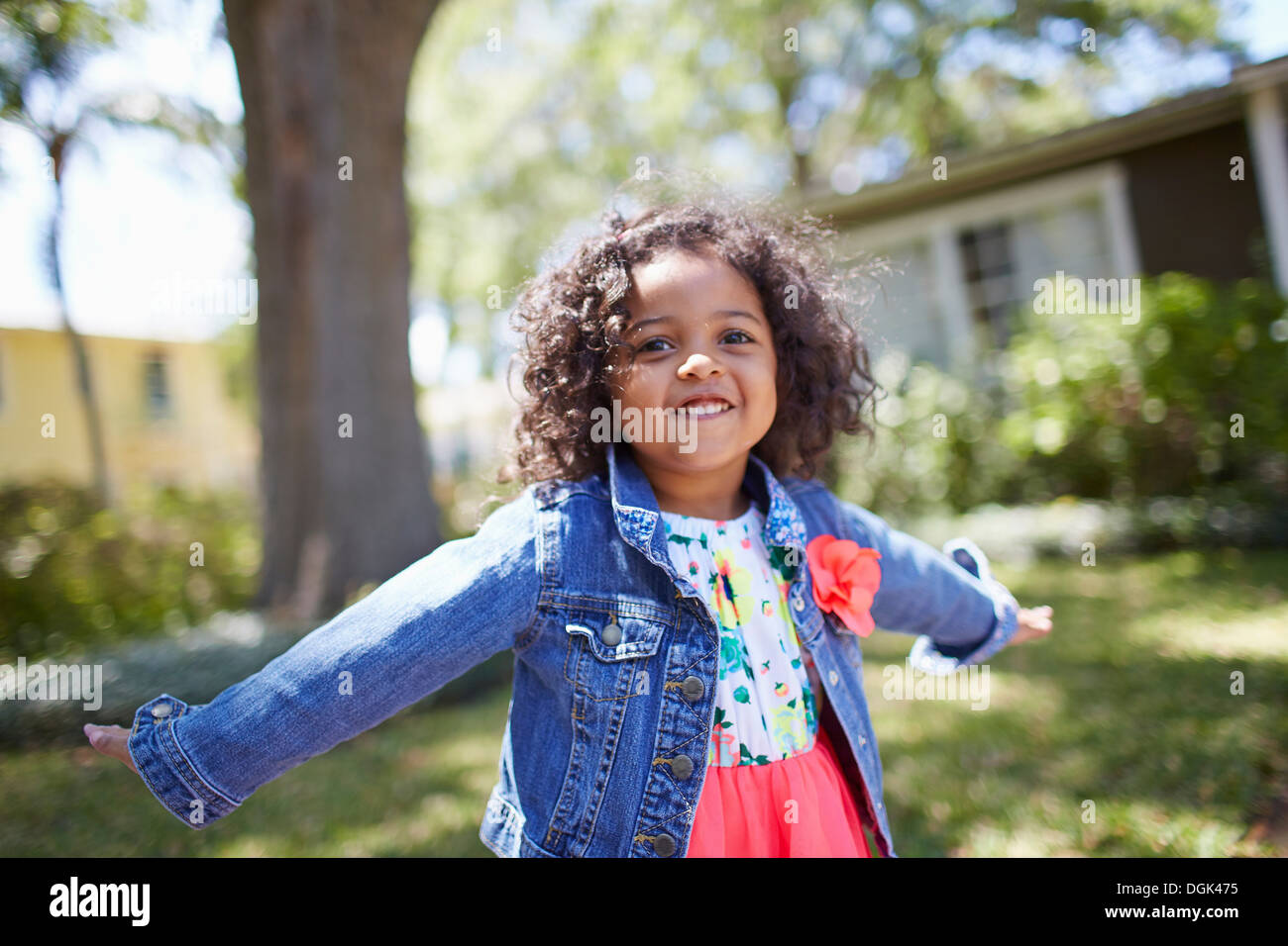 Girl standing in garden with arms wide - Stock Image