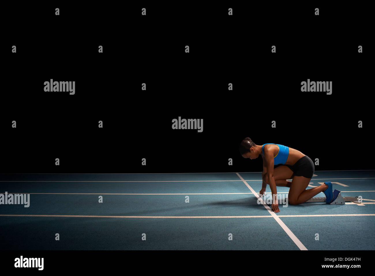 Young female athlete on starting blocks - Stock Image