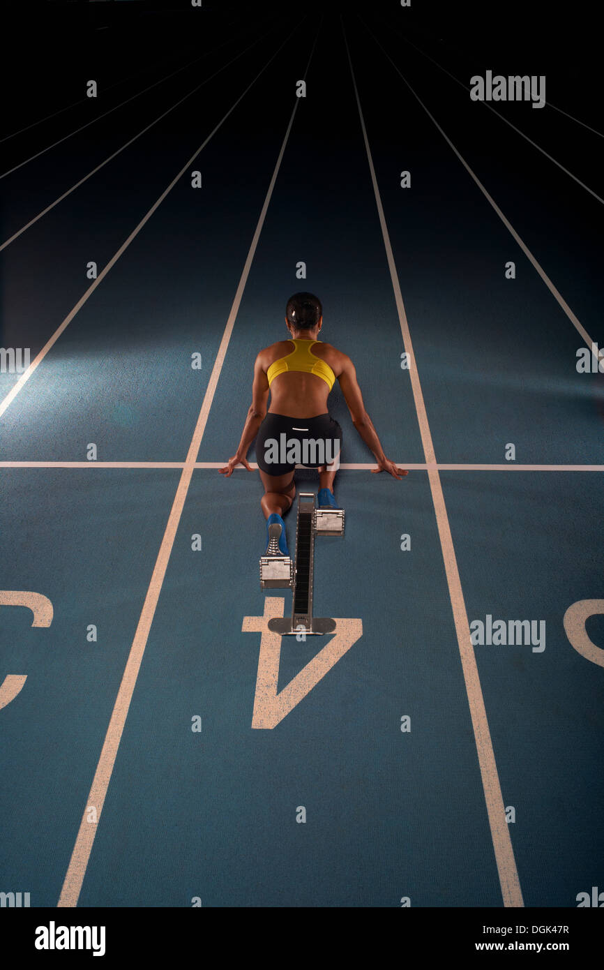 Young female athlete on starting blocks, high angle - Stock Image