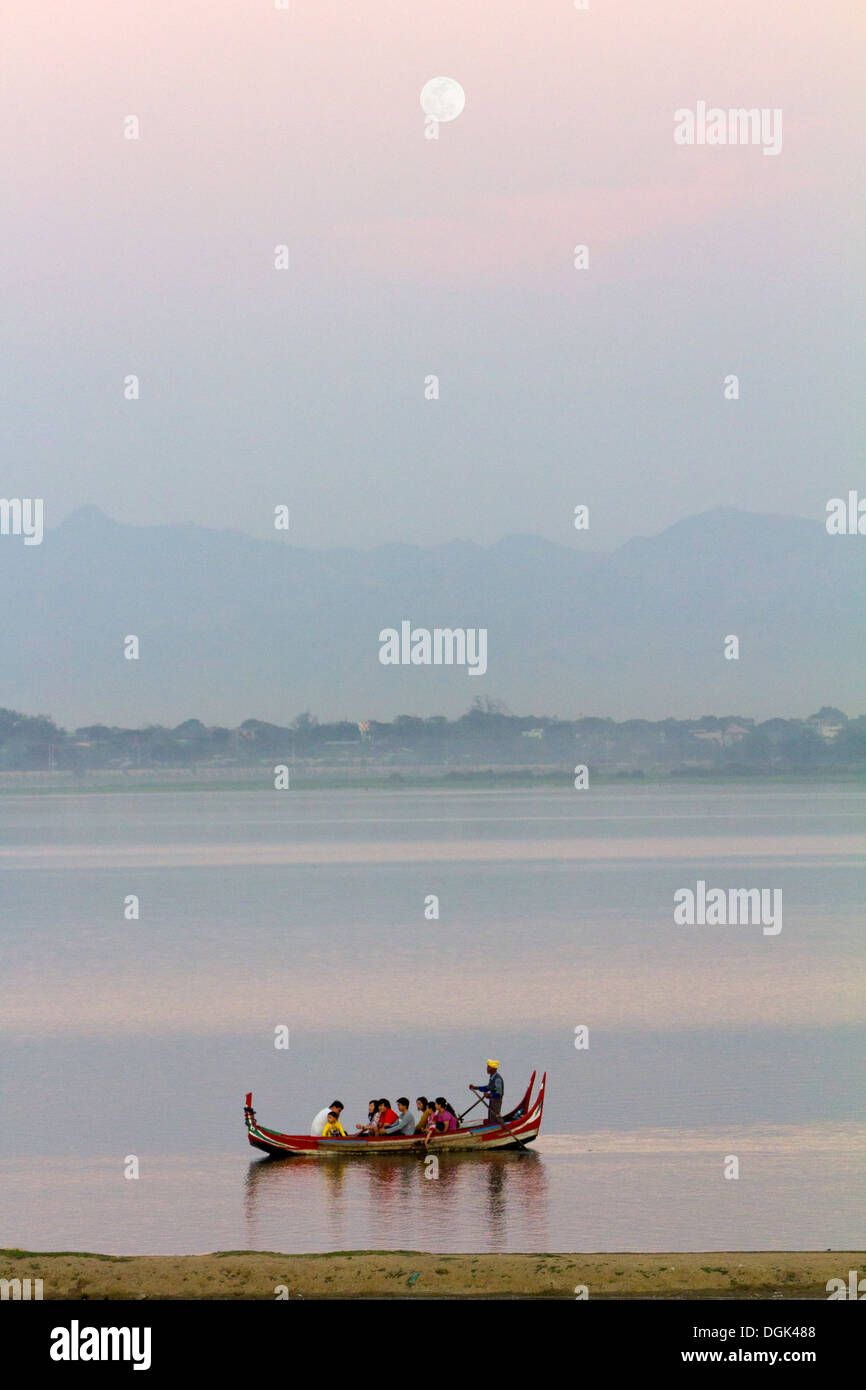 A full moon above Taungthaman Lake in Myanmar and late tourist boat going home. - Stock Image
