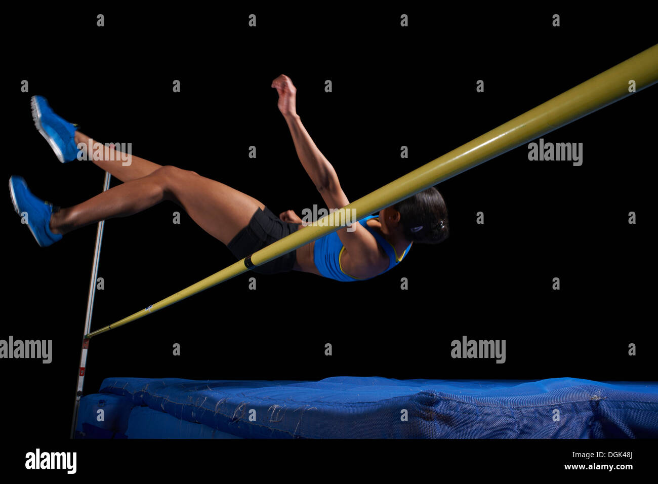 Young female athlete doing high jump - Stock Image