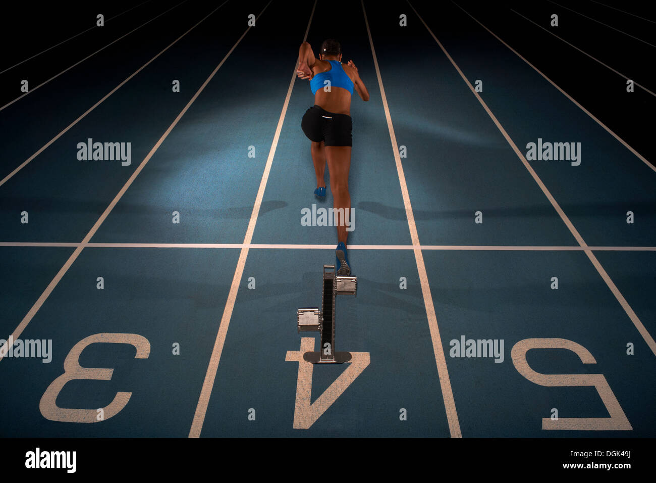 Young female athlete starting race, high angle - Stock Image