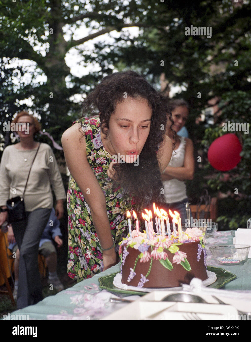 Young Lady Making A Wish And Blowing Out The Candles On Her 18th Birthday Cake MR