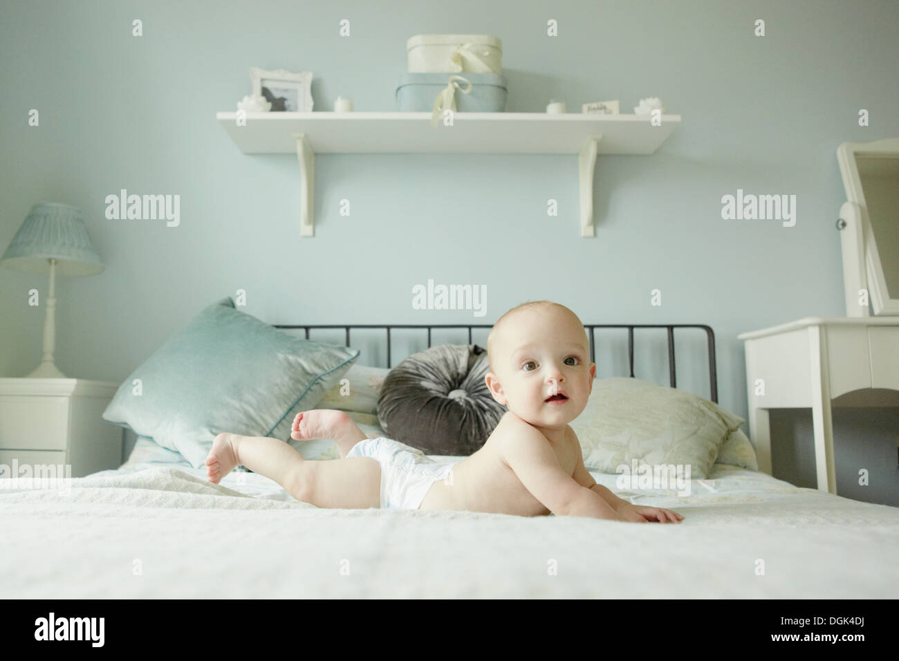 Baby boy lying on front on bed - Stock Image