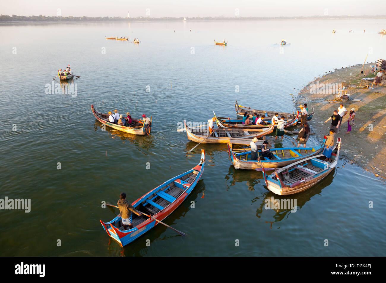 Tourist pleasure boats plying their trade by U Bein Teak Bridge across Taungthaman Lake in Myanmar. - Stock Image