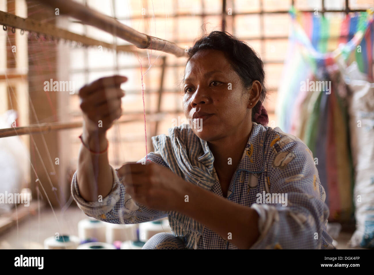 A women works in a small village textile factory outside of Phnom Penh, Cambodia. Photos © Dennis Drenner 2013. - Stock Image